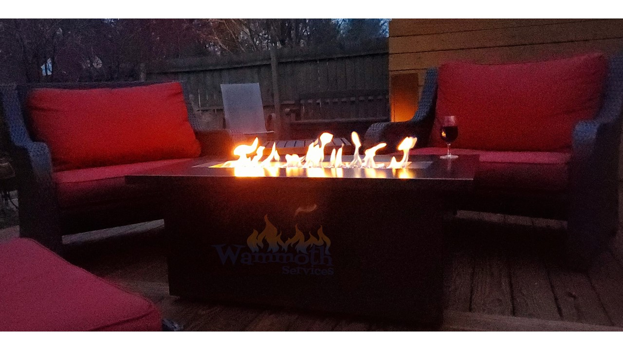Gas fireplace with red cushion furniture on a deck